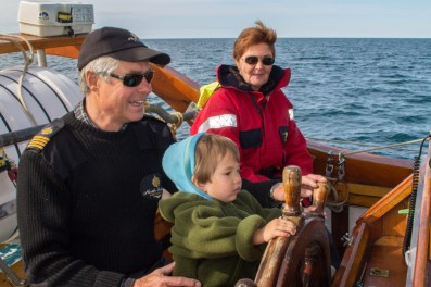 Young boy sits on a Captain's lap to steer a schooner