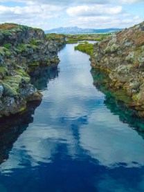 A river runs through rough volcanic rock reflecting the sky - Diving Iceland's Silfra