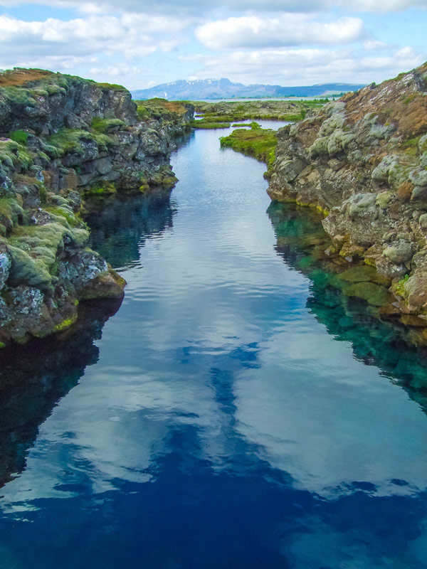 A narrow river among rocky terrain is the Silfra frissure in Iceland's Thingvellir National Park