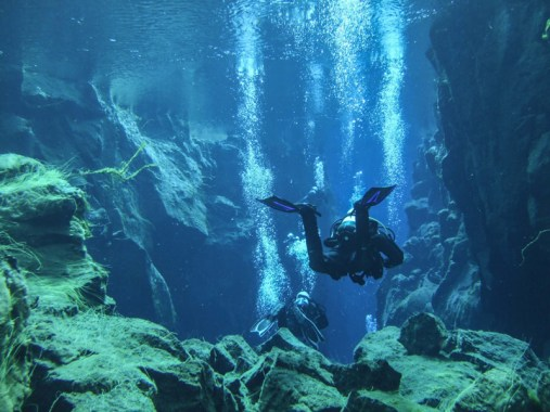 Two SCUBA divers float among bubbles in Silfra Iceland