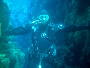 A SCUBA diver looks at the camera while touching two sides of a water filled crack - Diving Silfra's Fissure