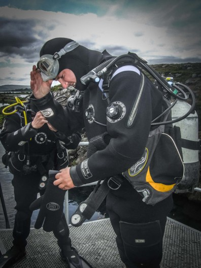 A man adjusts his SCUBA mask and dry suit before diving into the waters of Silfra Iceland