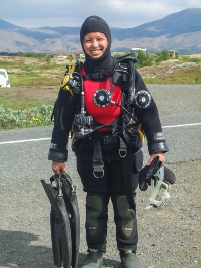An asian woman wearing a SCUBA dry suit poses for the camera - Diving Iceland's Silfra