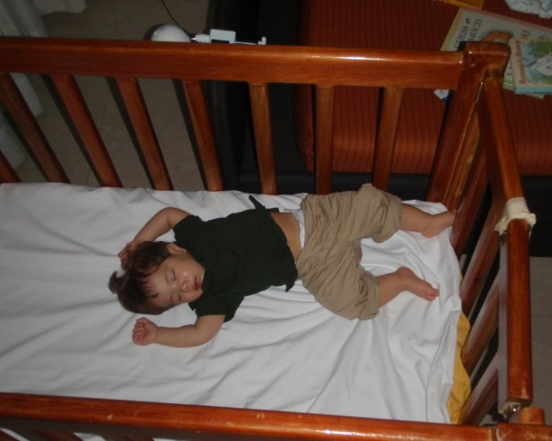 Child sleeping in a hotel crib - helping kids find nap time on the road