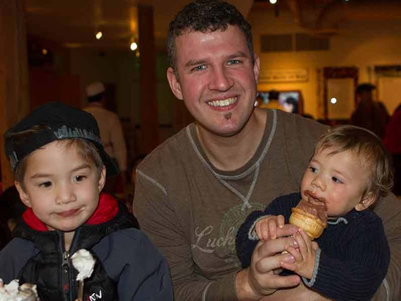 A father and his two young sons eat ice cream in San Francisco