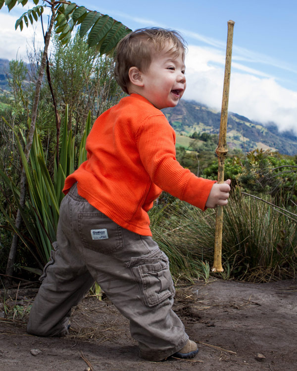 A toddler smiles proudly while brandishing a bamboo stick like a sword - Legend of El Dorado in Colombia
