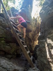 A woman climbs up a ladder in a small canyon - Limehouse Conservation Area