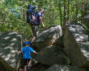 A father carrying a child in a backpack and his young son climb over rocks in the forest - Limehouse Conservation Area