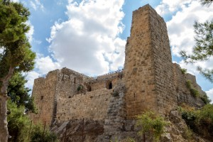 An ancient castle stands among trees against a blue sky - Traveling Jordan with Kids