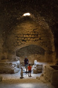 A woman and two young children stand in a beam of light from the roof of a castle - Traveling Jordan with Kids