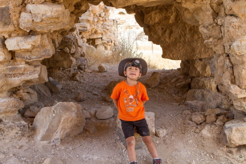 Young boy wearing a hat and headlamp poses in a castle tunnel