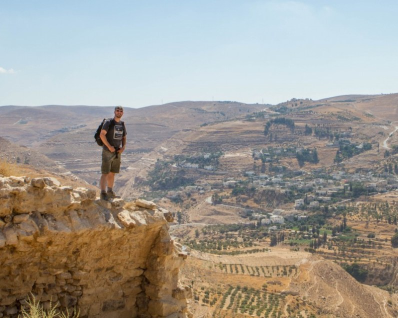 Man poses on a crumbling ledge of a castle looking out over a desert landscape