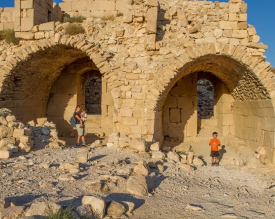 Young boy and a Mother and toddler pose in arches in a desert castle