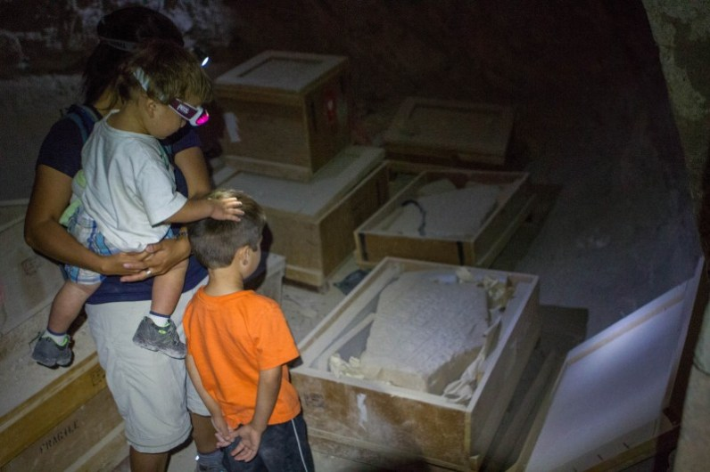 Mother and young children examine ancient artifacts in an ancient castle