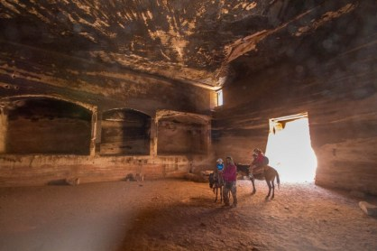 Family explores caves on horseback in Petra