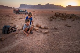Two young boys play with rocks in the desert while the sun sets