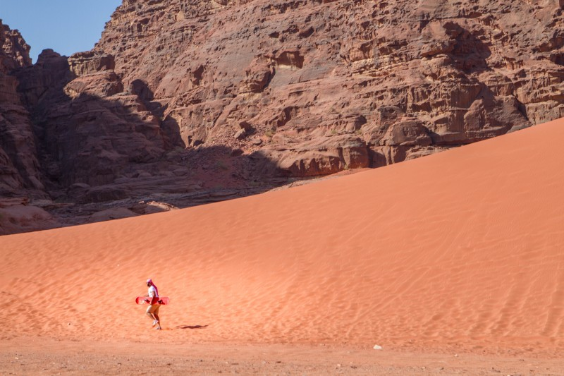 A man going sandboarding in Wadi Rum Jordan