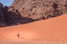 Man carrying a sandboard walks near a sand dune