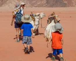 A guide introduce two young boys to camels in the desert - Traveling Jordan with Kids