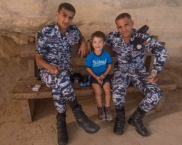 Young boy smiles between two Jordanian police officers while sitting on a bench - Traveling Jordan with Kids - Traveling Jordan with Kids
