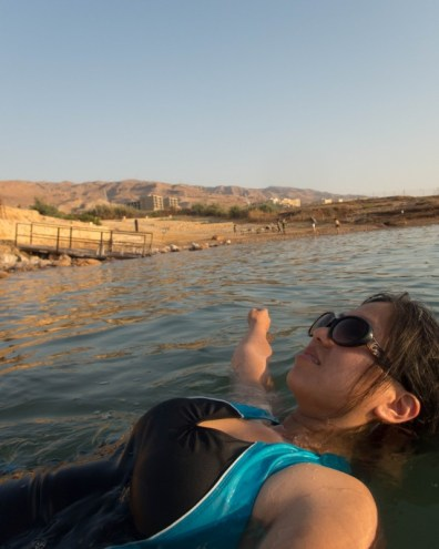 Woman wearing sunglasses floating in the Dead Sea at the Kempisnki Hotel