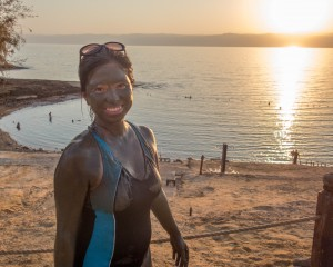 Woman covered in mud smiles in front of a sunset over the Dead Sea - Traveling Jordan with Kids