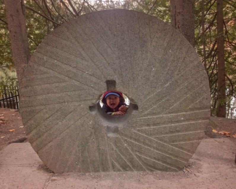 A young boy pokes his head through a grindstone