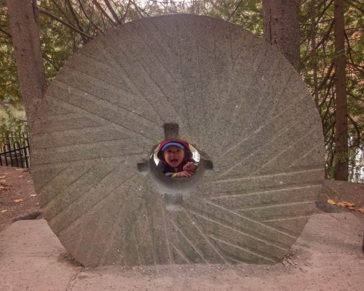 A young boy pokes his head through a grindstone