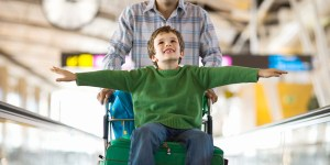 A smiling boy sitting on a luggage cart is pushed through an airport by his father