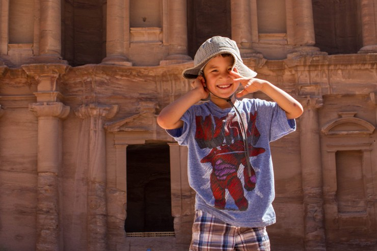 Amazing Experiences for Children in Jordan child standing in front of the Petra Monastery