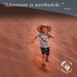 Young boy running down a red sand dune while laughing - Inspirational Quotes