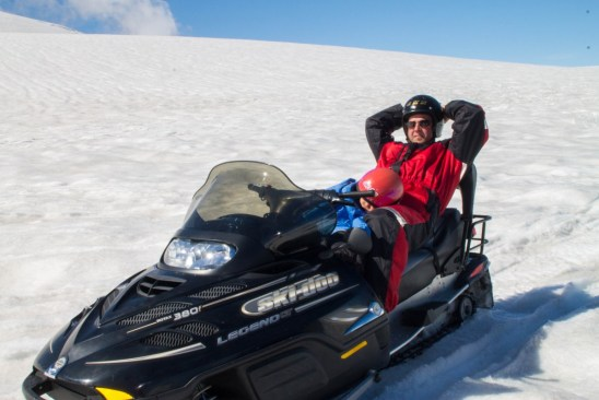 a man sits on a snowmobile on a glacier while a young boy naps in his lap