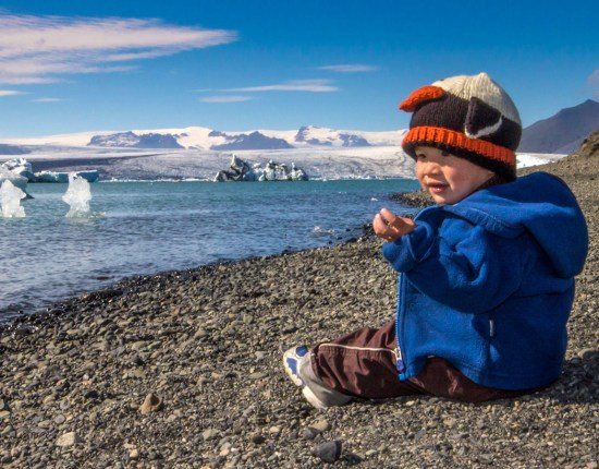 young boy sits on the shore of an iceberg filled lagoon