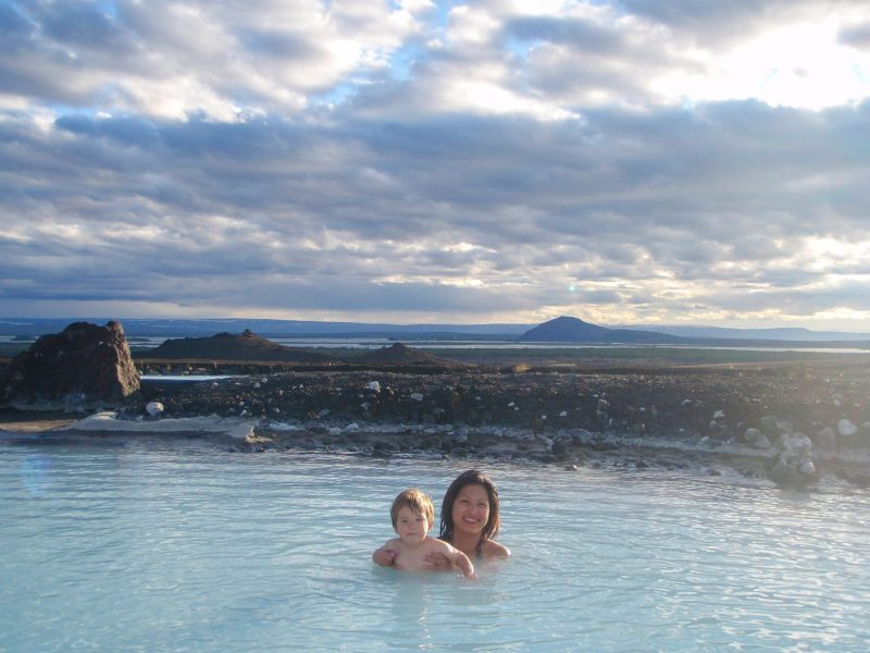a mother and young boy take a bath in the hot springs of Icelands Myvatn nature pools in Iceland for kids