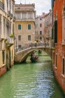 a lone gondola carries tourists through an empty river in Venice, Italy - Lost in Venice