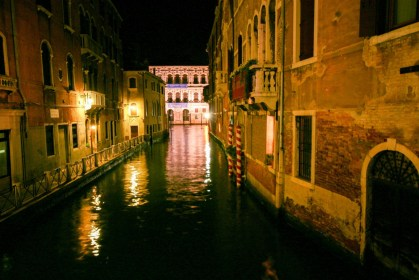 A river in Venice Italy at night is dotted with reflections of light from the surrounding buildings - Lost in Venice