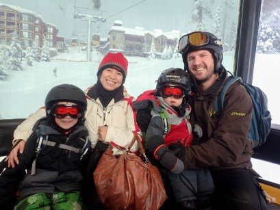 Interracial family of four in ski gear smiling - Learning to Ski at Kelowna's Big White