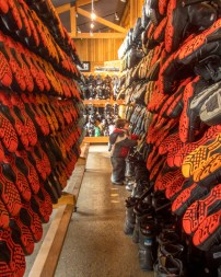 Young boy looks through racks of ski boots - Learning to Ski at Kelowna's Big White