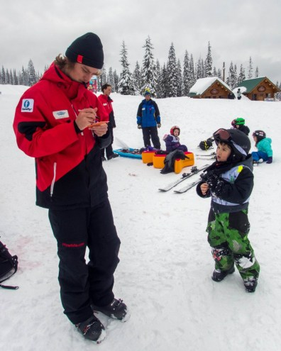 Young boy gets a report card from a ski instructor - Learning to Ski at Kelowna's Big White