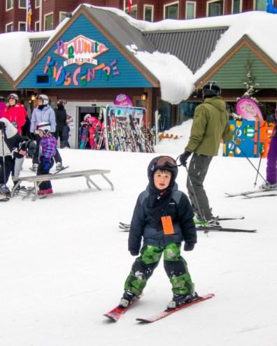 Young boy at a ski resort wearing ski gear - Learning to Ski at Kelowna's Big White