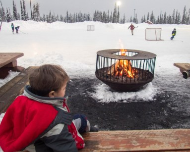 Young boy sits in front of a fire and watches a pond hockey game
