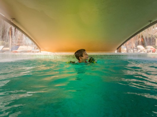 Young boy swimming under a bridge in a pool with water falling on both sides at the Kempinski Hotel