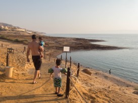 a father and two young boys walking down a rocky path to the Dead Sea at the Kempisnki Hotel
