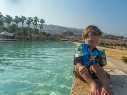 Toddler with water wings sits on the ledge of a pool with desert and palm trees in the background at the Kempinski Hotel