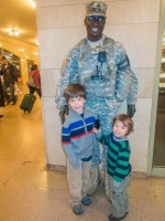 Two young boys smile with a soldier at Grand Central Station New York