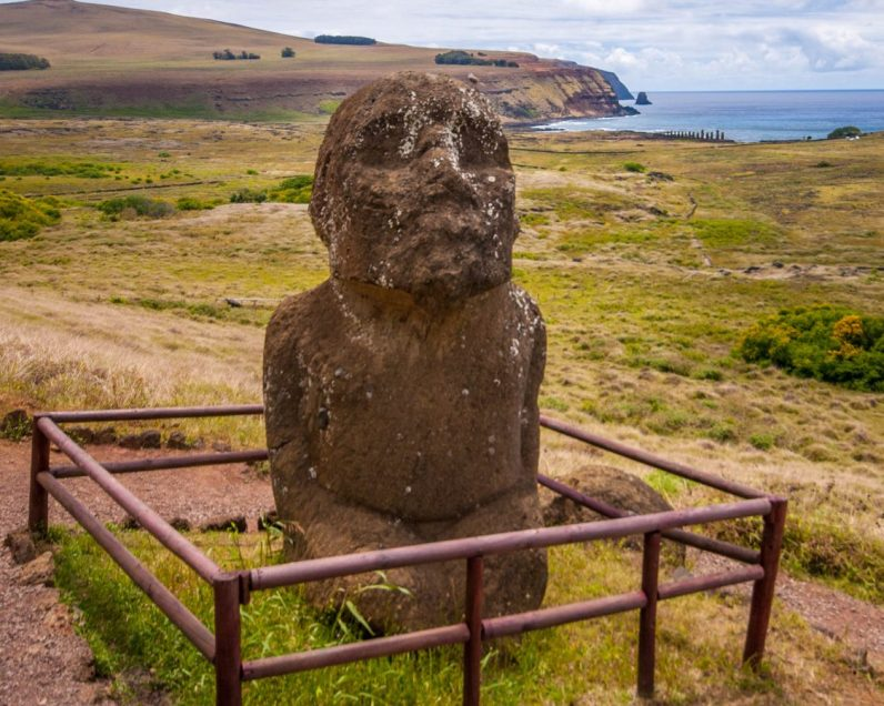 A unique moai sits in a fenced off area on a mountainside. The moai is kneeling and has a beard. In the background an ahu with 15 moai can be seen.