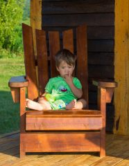 Little boy sitting on an adirondack chair while viewing the National Park of Bonaventure Island and Perce Rock.