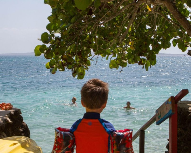 Young boy wearing water wings looking out over a tropical ocean