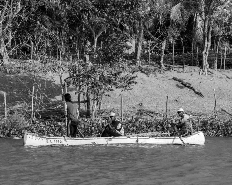 Men on a canoe fishing off of the waters of Pirate Island.