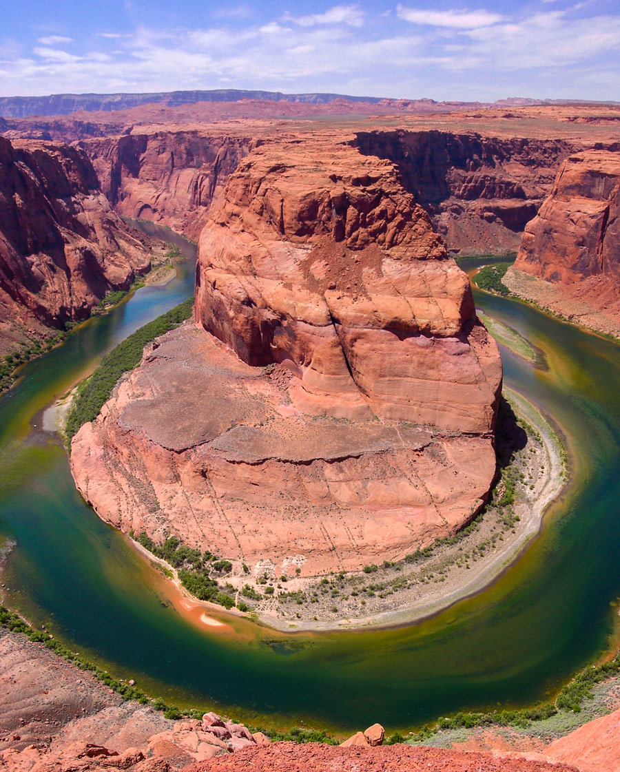 The green Colorado River bends around a tall red rock cliff in Utah - things to see in the American Southwest
